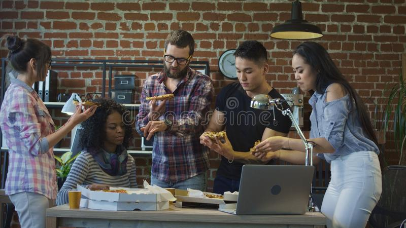 Colleagues in office eating pizza together stock photo