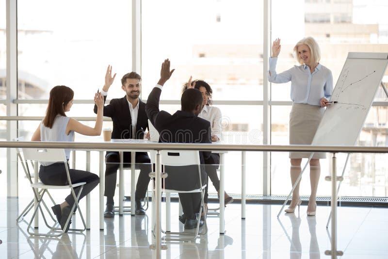 Diverse persone di affari felici e vettura che sollevano le mani all'ufficio t immagini stock