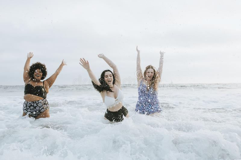 Diverse plus size women having fun in the water stock photography