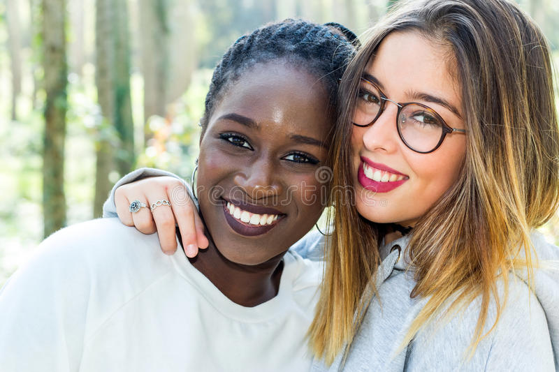 Diverse portrait of two attractive teen girlfriends outdoors. royalty free stock photo
