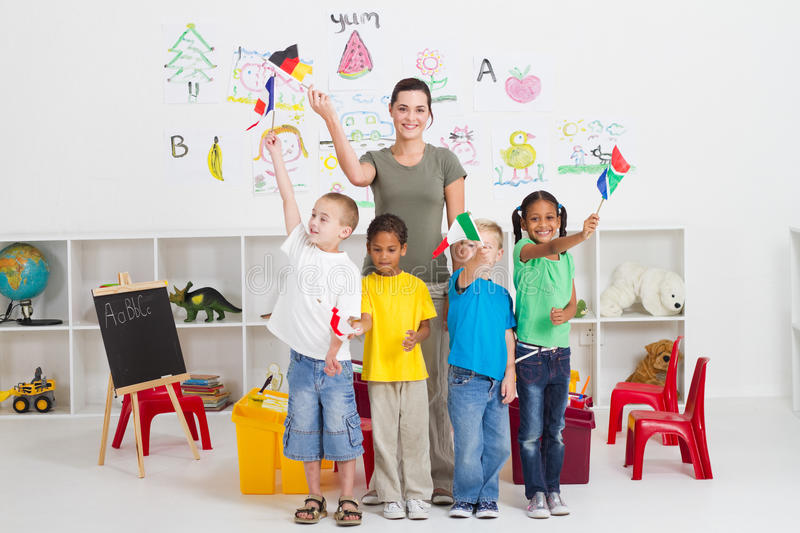 Diverse preschool students. A happy class of diverse nationalities preschool students waving flags in classroom royalty free stock images