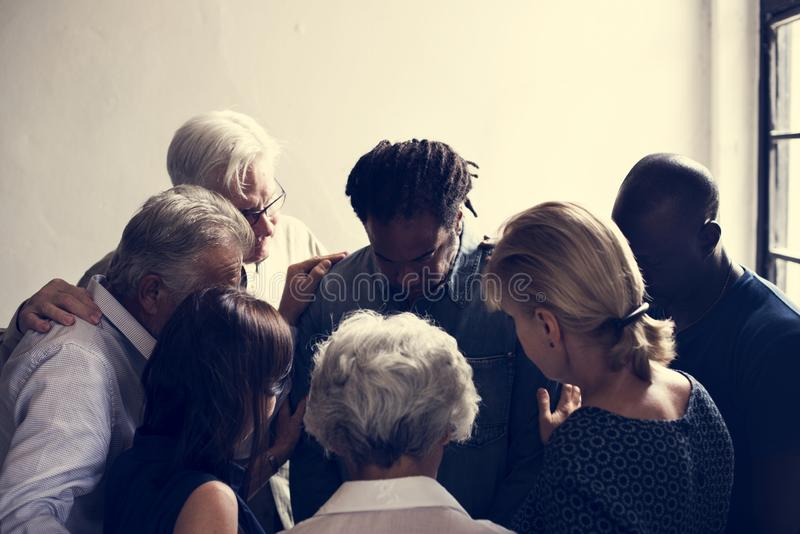 Diverse religious people praying together stock image