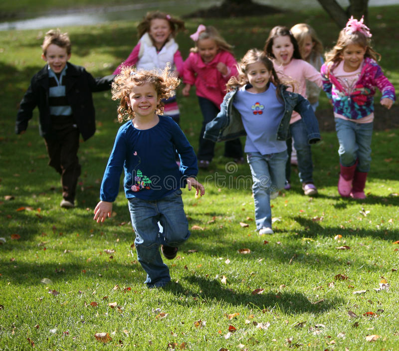 Diverse running kids. Group of diverse kids running outside in fall royalty free stock photo