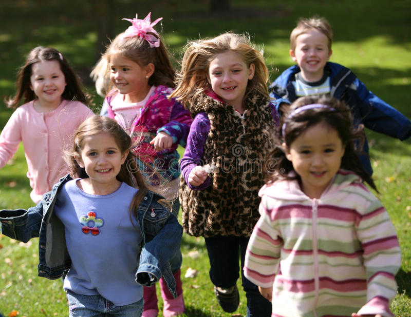 Diverse running kids. Group of diverse kids running outside in fall royalty free stock photography