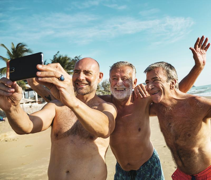 Diverse senior men taking the beach selfie royalty free stock photos