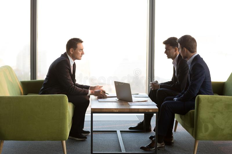 Diverse serious businessmen discuss new international project meeting investment adviser royalty free stock photo