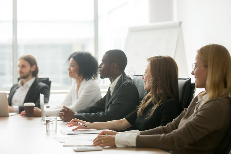 Diverse smiling businesspeople sitting at conference table at gr royalty free stock image