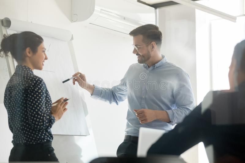 Diverse speakers make flip chart presentation in conference room stock photo