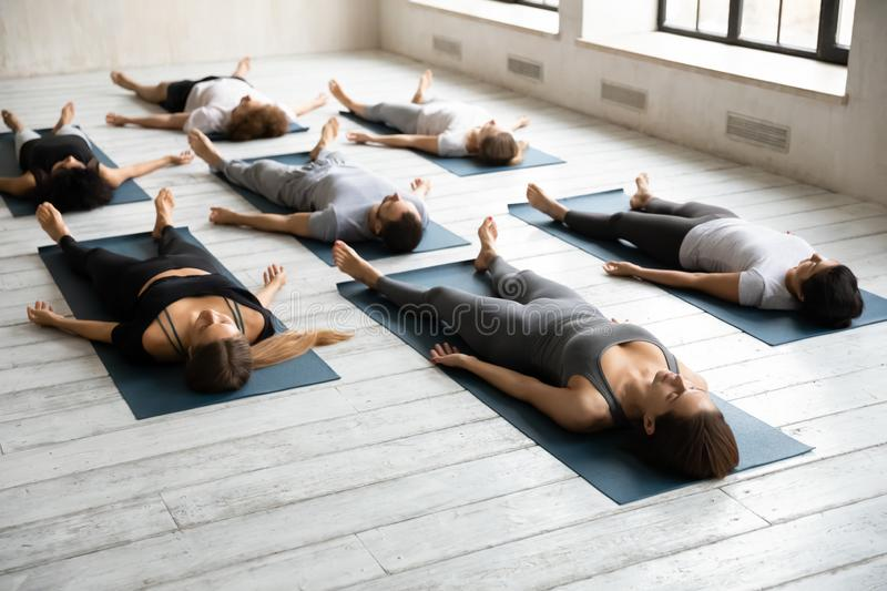 Diverse sporty people practicing yoga, relaxing in Savasana exercise. Diverse sporty young people practicing yoga at group lesson, relaxing in Savasana exercise stock photography