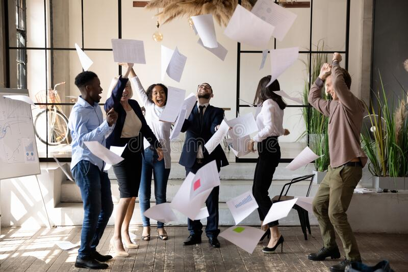 Diverse staff throwing papers up celebrating corporate success feels overjoyed royalty free stock photography