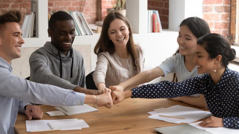 Diverse student stack hands together fists bumping showing unity royalty free stock images