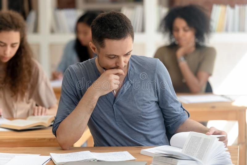 Diverse students absorbed reading textbook studying sitting at desks. Multi racial students girls guys sitting in rows at desks classroom absorbed reading stock photo