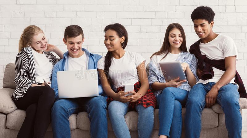 Diverse students preparing for exams with laptop and tablet stock image
