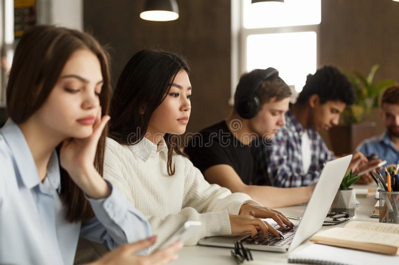 Diverse students sitting at college library, doing homework royalty free stock image