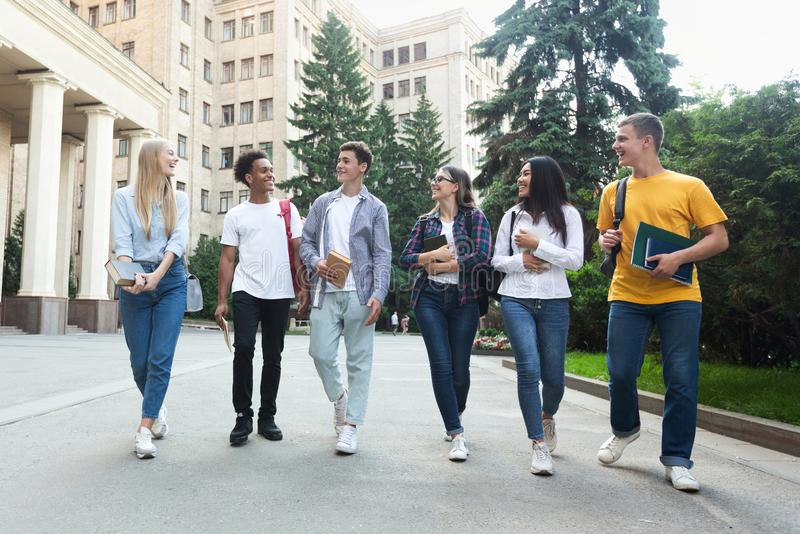 Diverse students walking outside the college building. And talking, having break after classes stock photos