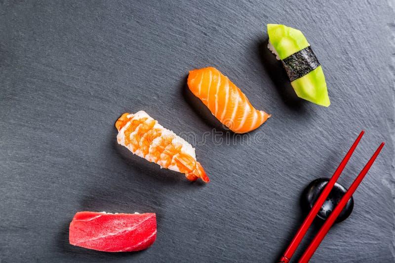 Diverse sushi op zwarte leiplaat met eetstokjes Japanse keuken royalty-vrije stock afbeelding