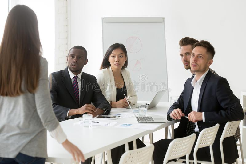 Diverse team being judgmental scolding unpunctual colleague royalty free stock photos