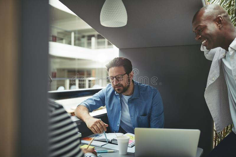 Diverse team of businessmen working in an office meeting pod stock photo
