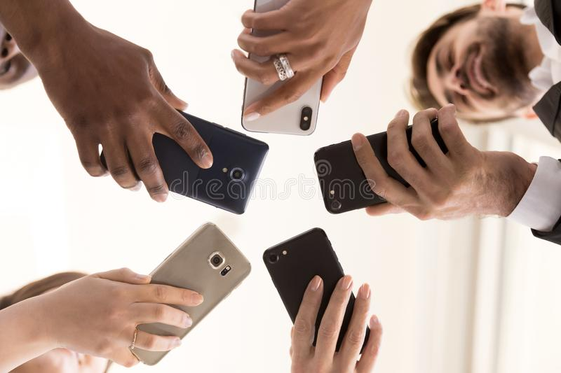 Diverse team employees using phones together bottom view stock photos