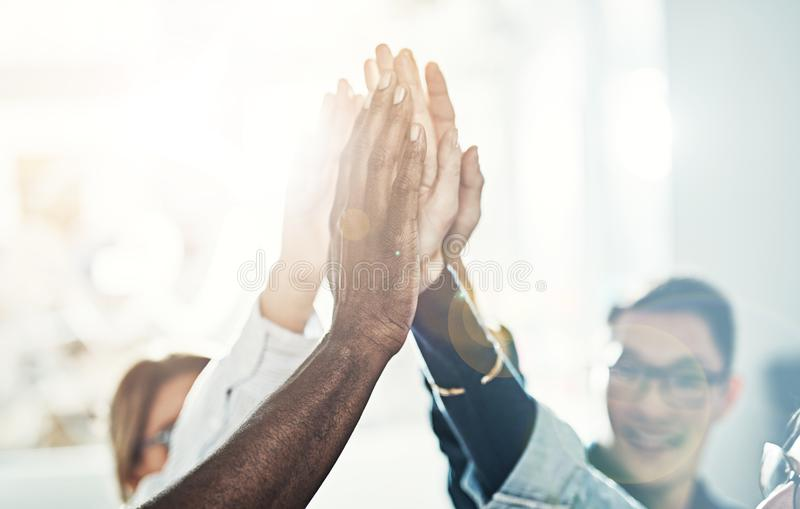 Diverse team of businesspeople high fiving together in an office royalty free stock image