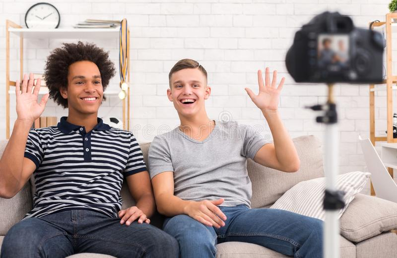 Diverse bloggers greeting their subscribers on camera. Diverse teen bloggers greeting their subscribers on camera at home royalty free stock photography