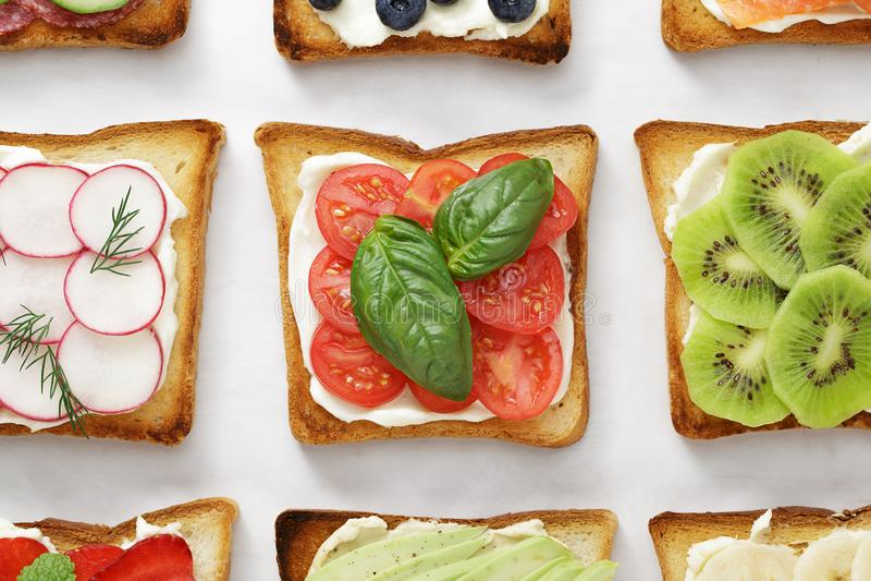 Diverse toosts met tomaten, basilicum, kaas, kiwi, radijs en andere bovenste laagjes op wit perkament royalty-vrije stock foto