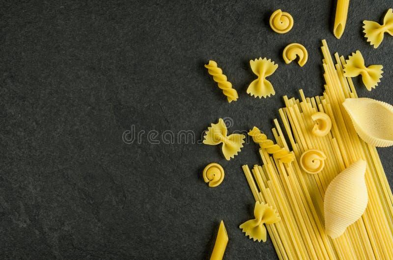 Diverse types van deegwaren op een lei stock foto's