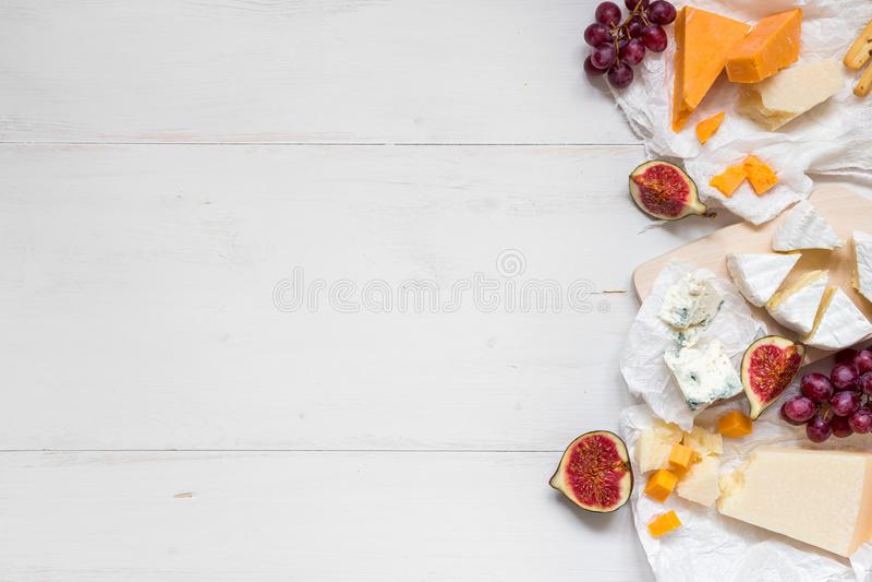 Diverse types van kaas met vruchten op de houten witte lijst met exemplaarruimte Hoogste mening stock afbeeldingen