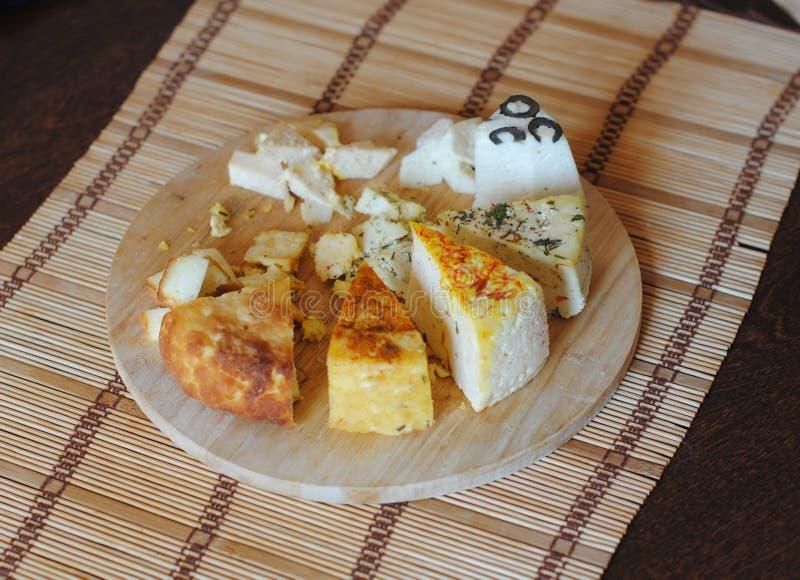 Diverse Types van Kaas op een Houten Achtergrond Geassorteerde ingelegde kazen op ronde houten raad op de mat stock foto