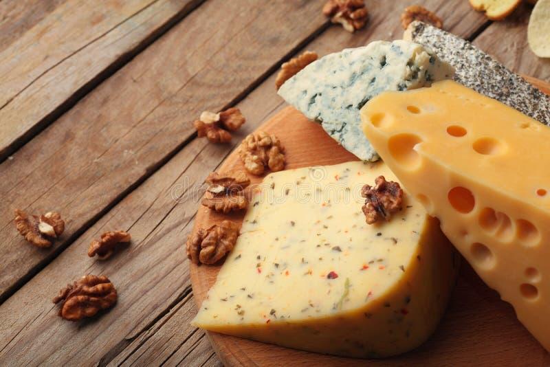 Diverse types van kaas op houten raad Chessnut De ruimte van het exemplaar royalty-vrije stock afbeeldingen