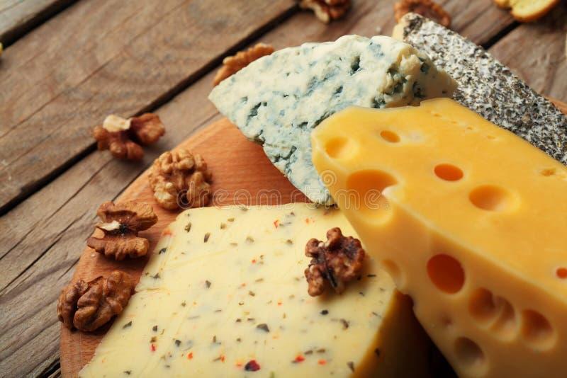 Diverse types van kaas op houten raad Chessnut De ruimte van het exemplaar royalty-vrije stock afbeelding