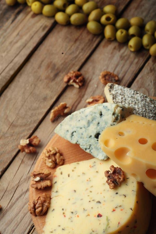 Diverse types van kaas op houten raad Chessnut OlivesCopyruimte royalty-vrije stock afbeeldingen