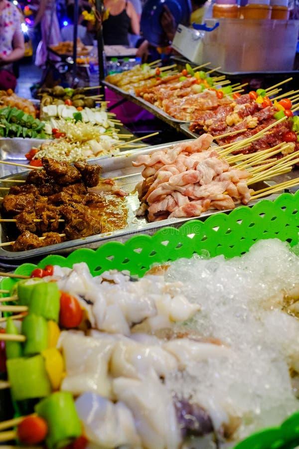 Diverse types van vlees zoals pijlinktvis, varkensvlees, kip, rundvlees en groenten zijn skewed voor het roosteren Geplaatst voor stock afbeeldingen