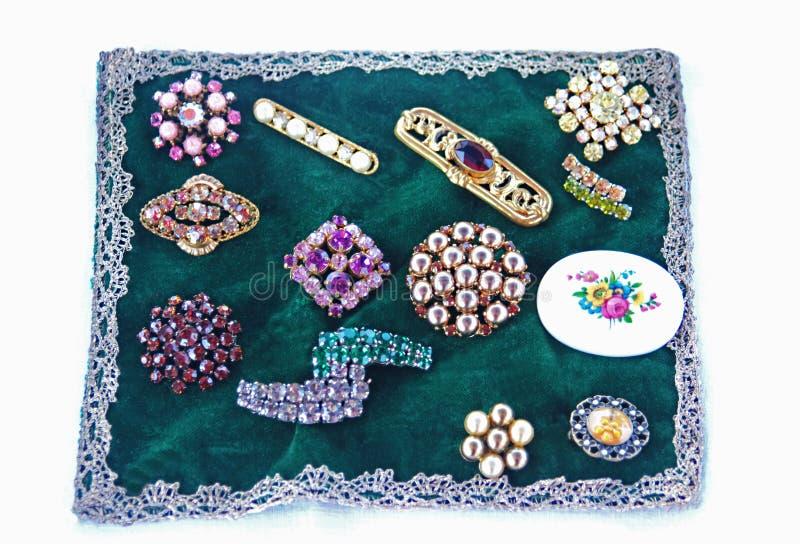 Diverse uitstekende broches op een groene fluweeldoek stock afbeelding