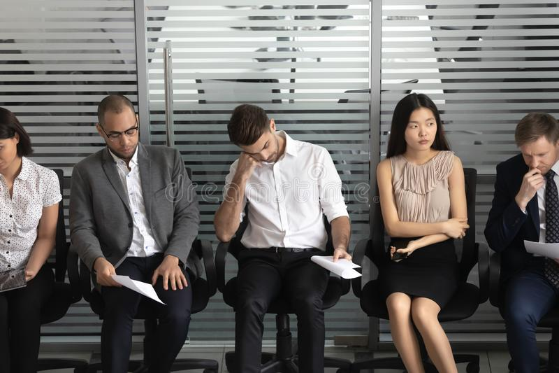 Diverse candidates waiting for job interview, people sitting in row royalty free stock images