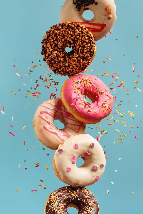 Diverse verfraaide doughnuts in motie die op blauwe achtergrond vallen royalty-vrije stock fotografie