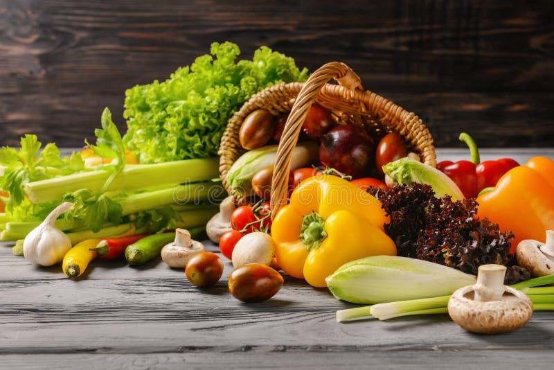 Diverse verse groenten met rieten mand op houten lijst stock fotografie