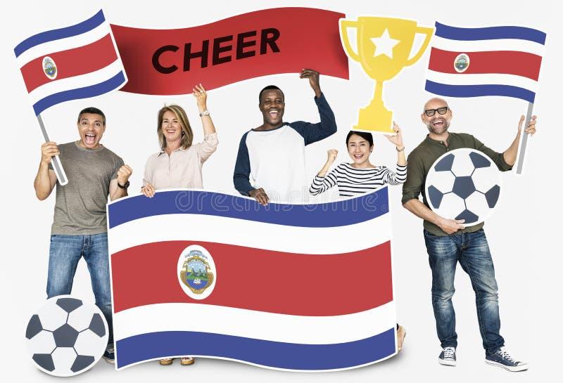 Diverse voetbalventilators die de vlag van Costa Rica houden royalty-vrije stock foto