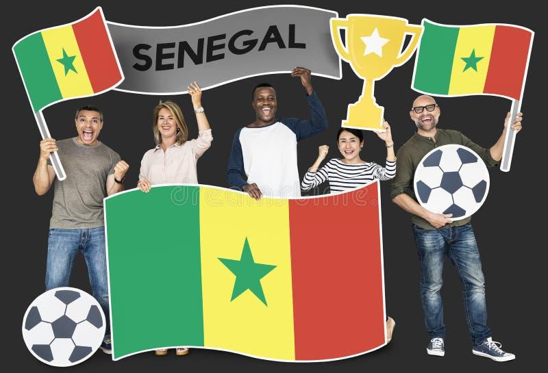 Diverse voetbalventilators die de vlag van Senegal houden stock fotografie