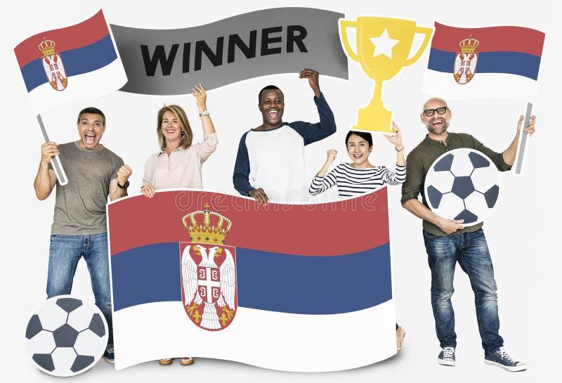 Diverse voetbalventilators die de vlag van Servië houden royalty-vrije stock foto