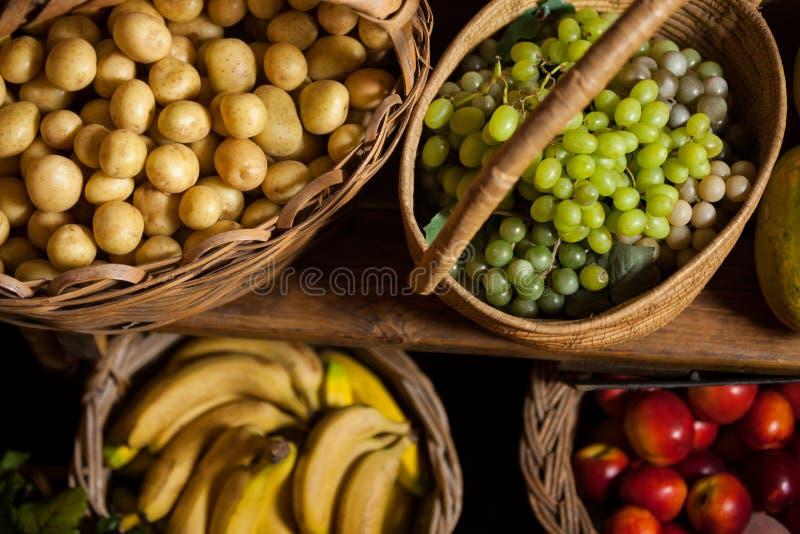 Diverse vruchten en groenten in rieten mand bij organische sectie stock foto