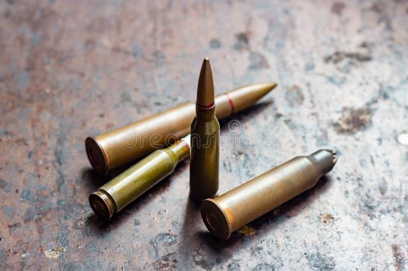 Diverse weapon bullets on rusty metal background. Military industry, war, global arms trade and crime concept. Diverse weapon bullets on rusty metal background stock photo