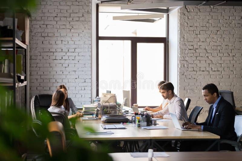 Diverse werknemers bezig het werken in gedeeld bureau stock afbeelding