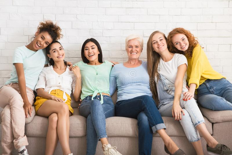Diverse Women Hugging Sitting On Couch Against White Wall Indoor royalty free stock images
