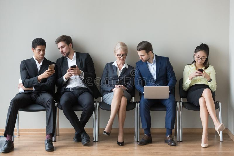 Diverse work candidates sit in queue using gadgets before interv stock image