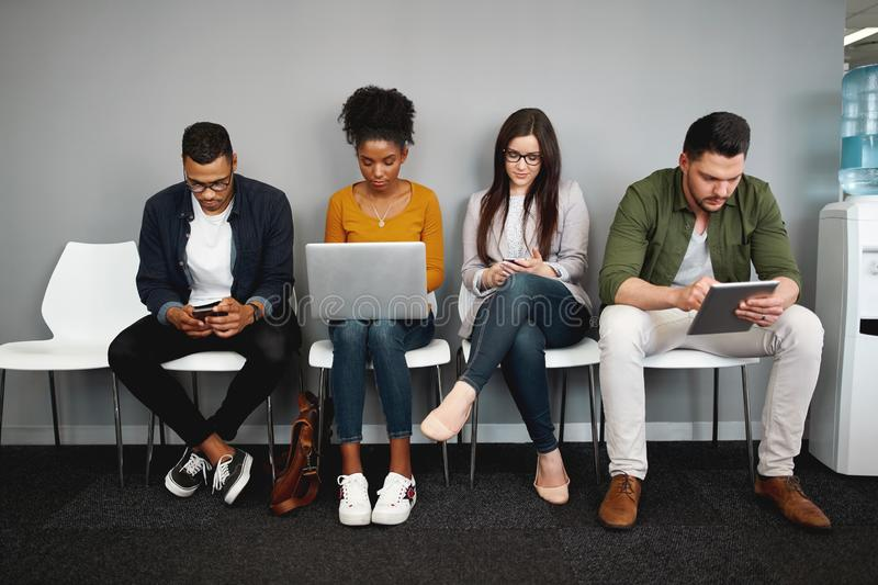 Diverse work candidates sitting in queue in office for job interview using modern gadgets preparing for recruiting royalty free stock photos