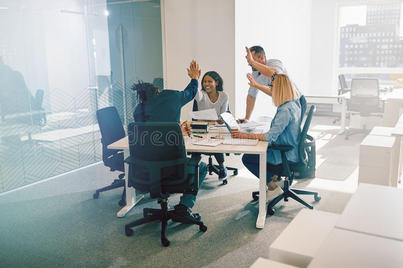 Diverse work colleagues excitedly high fiving during an office m stock images