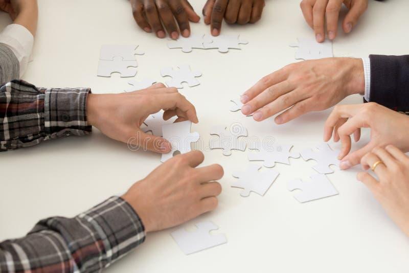 Diverse work team assembling jigsaw at teambuilding activity stock photography
