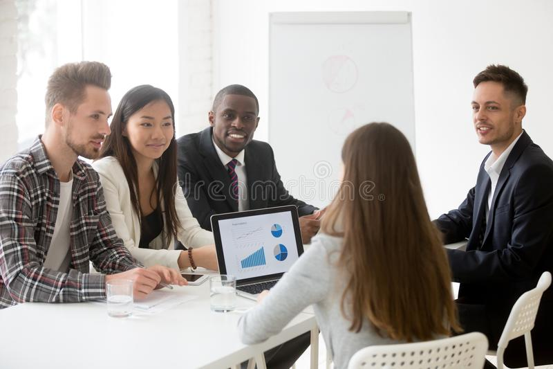 Diverse work team listening to female leader explaining strategy stock photos