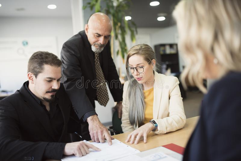 Diverse work team in office looking files at table royalty free stock photography